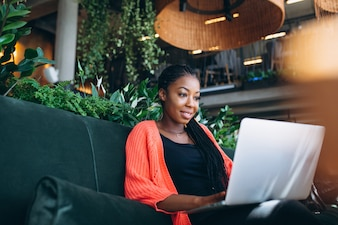 African american woman with laptop in a cafe