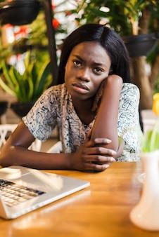 カフェでラップトップを持つアフリカ系アメリカ人の女性