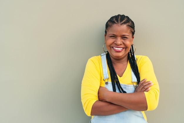 Афро-американская женщина с длинными волосами и косами стоит на серой стене - счастье