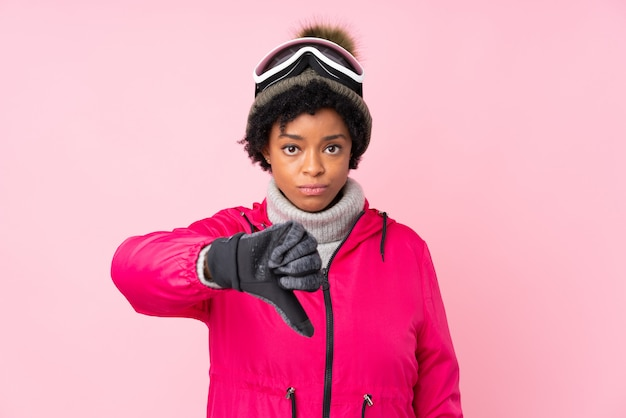 African american woman with ski glasses over isolated pink wall