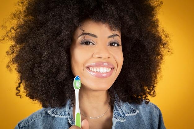 歯ブラシを持つアフリカ系アメリカ人の女性。きれいな健康な歯、歯科治療、黄色の背景