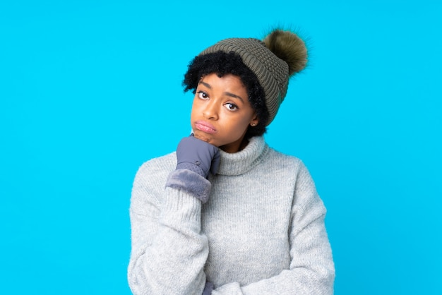 African american woman with winter hat over isolated blue wall