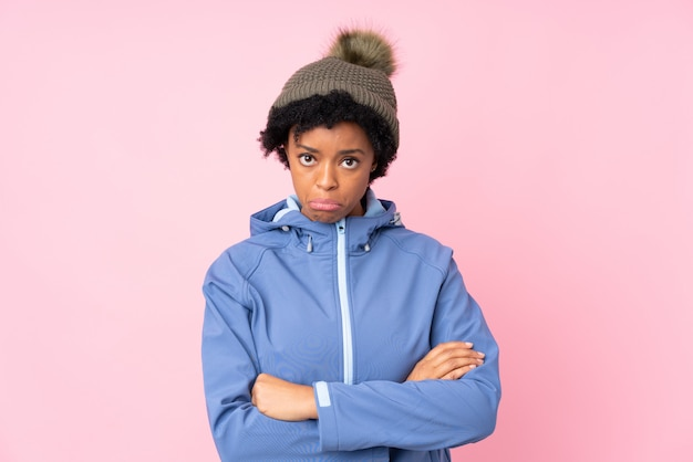 African american woman with winter hat over isolated pink wall