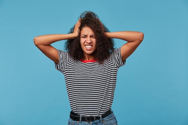 アフリカ系アメリカ人の女性女性は何か素晴らしいことを覚えていて、両手を頭に置いています