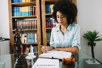 African American woman writing in book at table in office