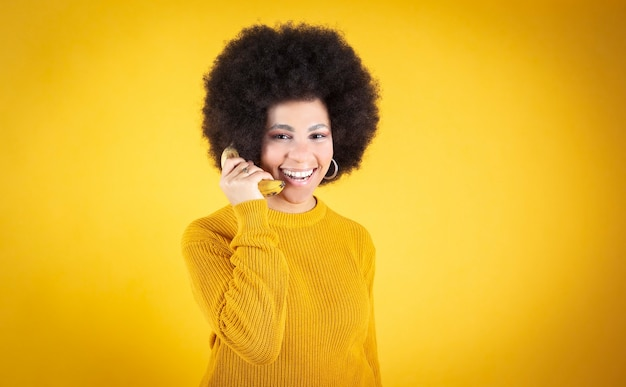 African american woman wsing a banana as a phone on yellow background