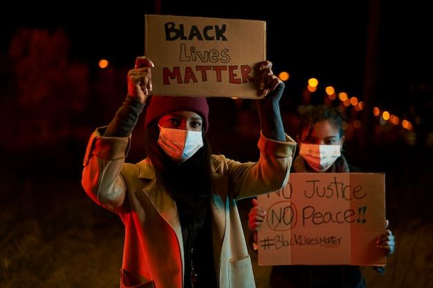 Афро-американские женщины проводят демонстрацию против расизма. демонстранты в городе со знаменами борются за свои права. жизни темнокожих имеют значение.