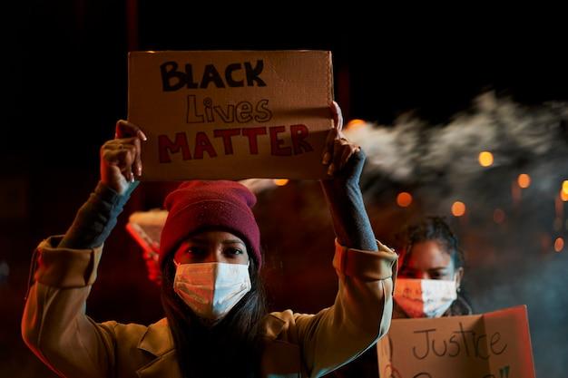 Афро-американские женщины проводят демонстрацию против расизма. демонстранты в городе со знаменами борются за свои права.