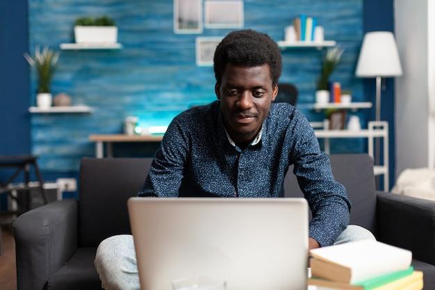 거실에서 화상 통화 회의를 하는 아프리카계 미국인 직원이 온라인 인터넷으로 이야기하고 있습니다.