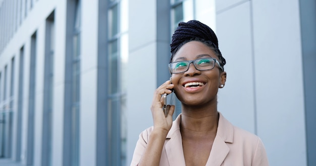 携帯電話で話し、ビジネスセンターで外で笑っている眼鏡をかけたアフリカ系アメリカ人の若い美しい陽気な女性。携帯電話で話す眼鏡の幸せな実業家。会話。