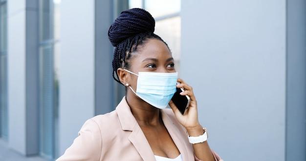 携帯電話で話し、ビジネスセンターで外を歩いている医療マスクのアフリカ系アメリカ人の若い美しい女性。携帯電話で話したり散歩したりする呼吸保護の幸せな実業家