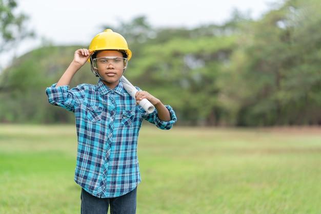 青写真を保持しているエンジニアの帽子のアフリカ系アメリカ人の少年