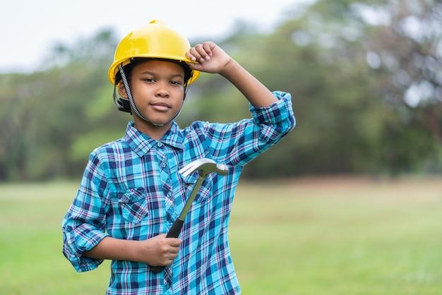ハンマーを保持しているエンジニアの帽子のアフリカ系アメリカ人の少年