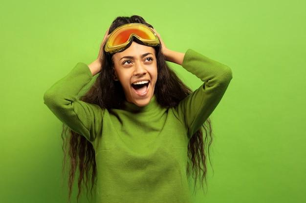 녹색 스튜디오 배경에 스키 마스크에 아프리카 계 미국인 젊은 갈색 머리 여자의 초상화. 인간의 감정, 표정, 판매, 광고, 겨울 스포츠 및 휴일의 개념. 놀란 비명.