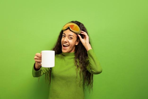 緑のスタジオの背景にスキーマスクでアフリカ系アメリカ人の若いブルネットの女性の肖像画。人間の感情、顔の表情、販売、広告、ウィンタースポーツ、休日の概念。お茶やコーヒーを飲む。