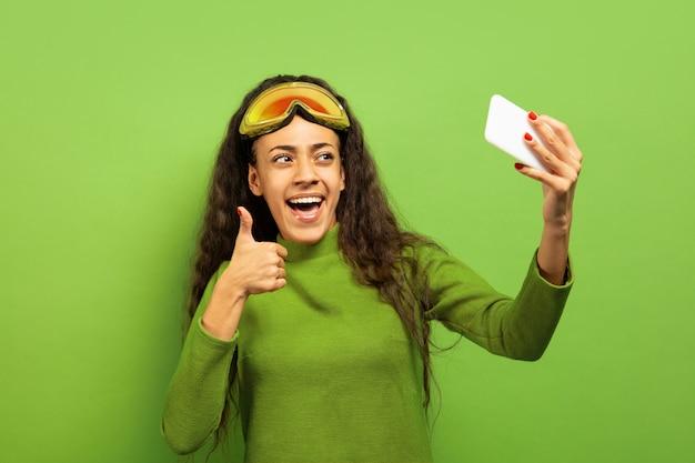 녹색 스튜디오 배경에 스키 마스크에 아프리카 계 미국인 젊은 갈색 머리 여자의 초상화. 인간의 감정, 표정, 판매, 광고, 겨울 스포츠 및 휴일의 개념. 셀카 또는 동영상 블로그 만들기.
