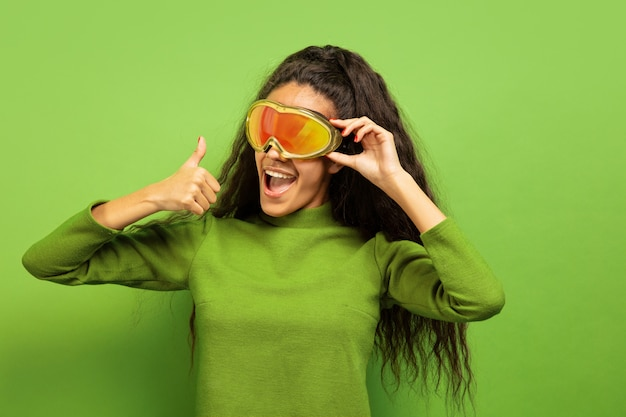 緑のスタジオの背景にスキーマスクでアフリカ系アメリカ人の若いブルネットの女性の肖像画。人間の感情、顔の表情、販売、広告、ウィンタースポーツ、休日の概念。笑顔、親指を立てる。