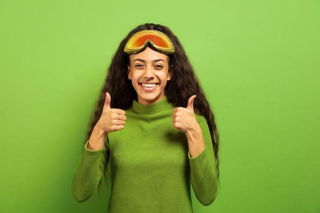 녹색 스튜디오 배경에 스키 마스크에 아프리카 계 미국인 젊은 갈색 머리 여자의 초상화. 인간의 감정, 표정, 판매, 광고, 겨울 스포츠 및 휴일의 개념. 웃고, 위로 엄지.