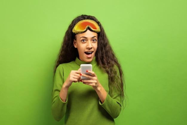 Портрет афро-американской молодой брюнетки в лыжной маске на зеленом фоне студии. концепция человеческих эмоций, выражения лица, продаж, рекламы, зимних видов спорта и праздников. используя смартфон.