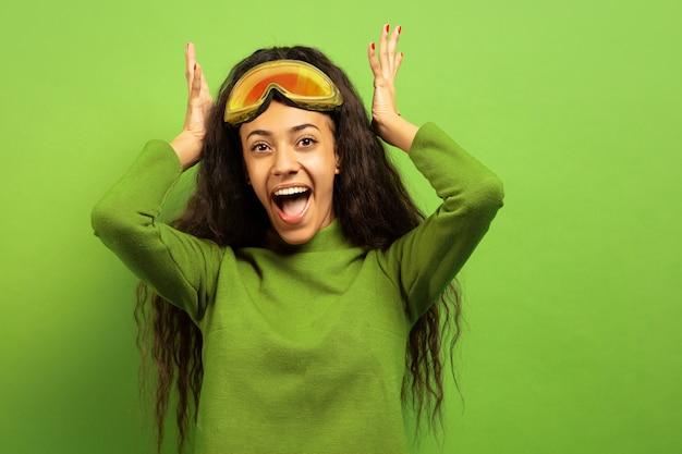 Портрет афро-американской молодой брюнетки в лыжной маске на зеленом