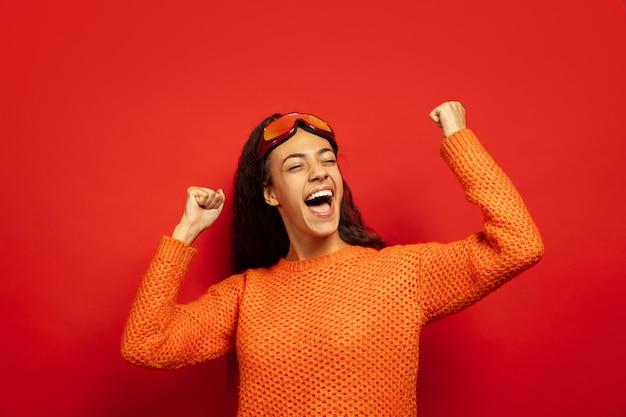 赤いスタジオの背景にスキーマスクでアフリカ系アメリカ人の若いブルネットの女性の肖像画。人間の感情、顔の表情、販売、広告、ウィンタースポーツ、休日の概念。勝者のように祝います。