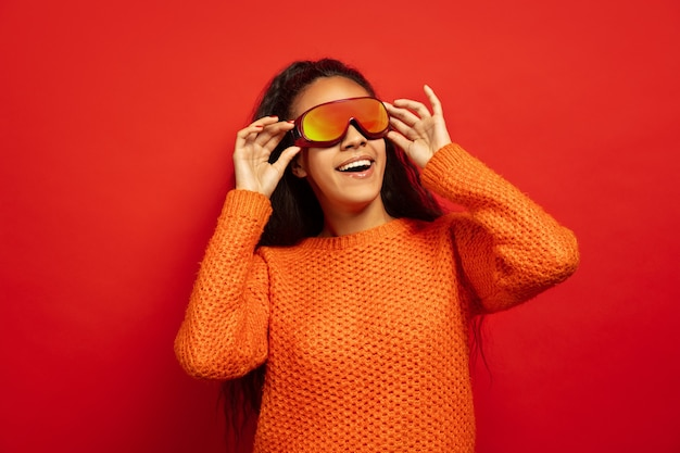 赤いスタジオの背景にスキーマスクでアフリカ系アメリカ人の若いブルネットの女性の肖像画。人間の感情、顔の表情、販売、広告、ウィンタースポーツ、休日の概念。見上げて、笑って。
