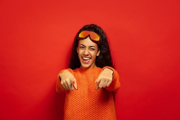 Портрет афро-американской молодой брюнетки в лыжной маске на красном фоне студии. концепция человеческих эмоций, выражения лица, продаж, рекламы, зимних видов спорта и праздников. указывая на, смеясь.