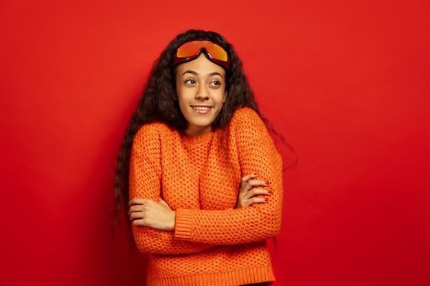赤いスタジオの背景にスキーマスクでアフリカ系アメリカ人の若いブルネットの女性の肖像画。人間の感情、顔の表情、販売、広告、ウィンタースポーツ、休日の概念。笑顔で、横を見て。