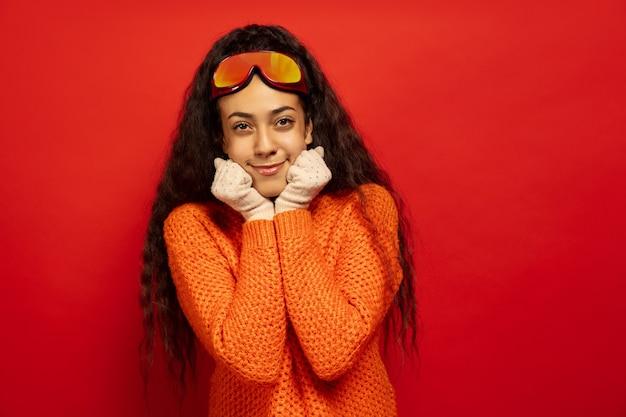 Портрет афро-американской молодой брюнетки в лыжной маске на красном фоне студии. концепция человеческих эмоций, выражения лица, продаж, рекламы, зимних видов спорта и праздников. улыбается, мило выглядит.