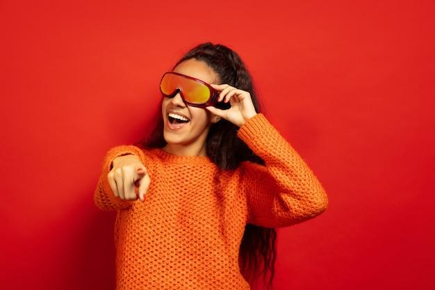 Портрет афро-американской молодой брюнетки в лыжной маске на красном фоне студии. концепция человеческих эмоций, выражения лица, продаж, рекламы, зимних видов спорта и праздников. улыбаясь, указывая на.