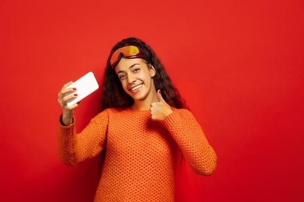 Портрет афро-американской молодой брюнетки в лыжной маске на красном