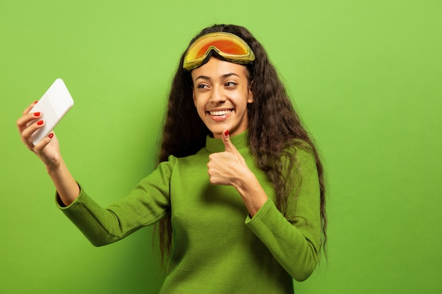 African-american young brunette woman's portrait in ski mask on green studio background. concept of human emotions, facial expression, sales, ad, winter sport and holidays. making selfie or vlog.