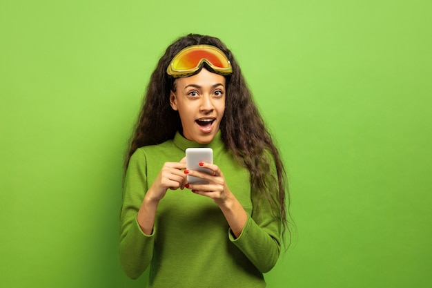 African-american young brunette woman's portrait in ski mask on green studio background. concept of human emotions, facial expression, sales, ad, winter sport and holidays. using smartphone.