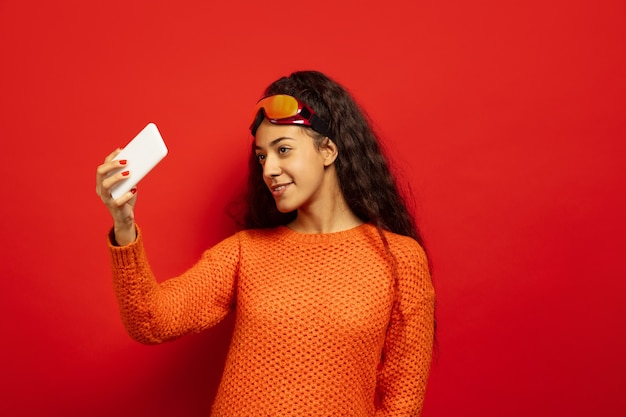 African-american young brunette woman's portrait in ski mask on red studio background. concept of human emotions, facial expression, sales, ad, winter sport and holidays. drinks tea, coffee.