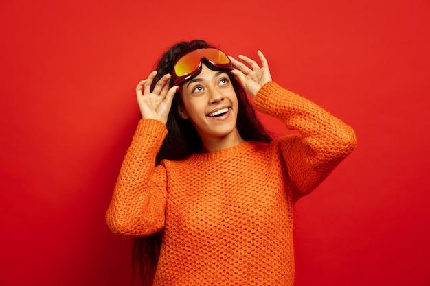 Ritratto di giovane donna bruna afro-americana in passamontagna sul rosso