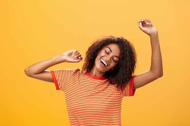 Афро-американская молодая женщина в полосатой футболке протягивает руки вверх, закрывает глаза от восторга и улыбается над оранжевой стеной
