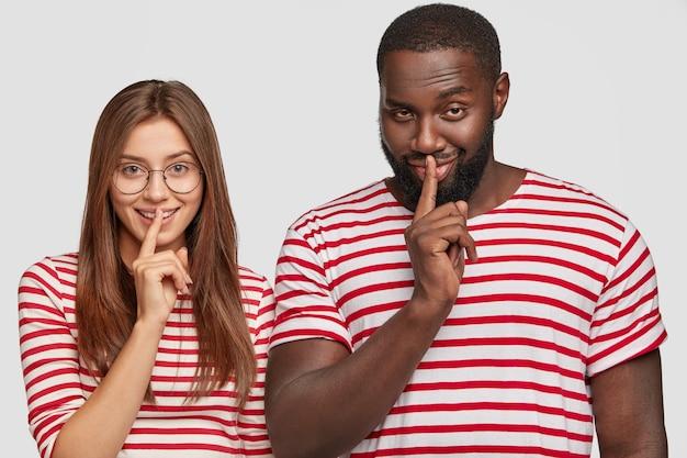 Il giovane ragazzo afroamericano e la ragazza europea fanno il gesto del silenzio, tengono il dito indice sulla bocca