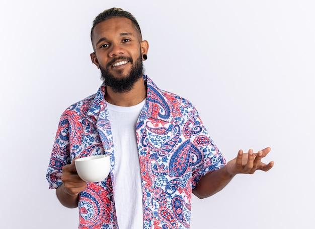 Giovane afroamericano in camicia colorata che tiene tazza felice e positivo sorridente allegramente in piedi su sfondo bianco