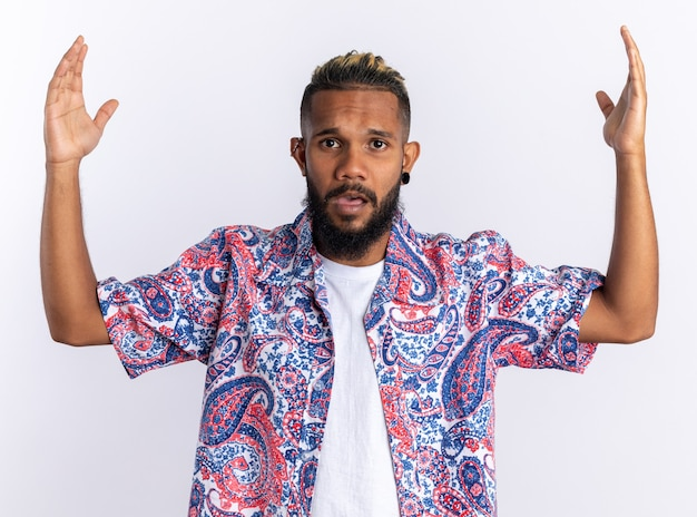 African american young man in colorful shirt looking at camera confused and displeased raising arms in indignation standing over white background