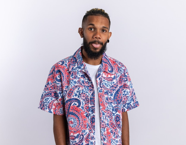African american young man in colorful shirt looking at camera happy and positive sticking out tongue