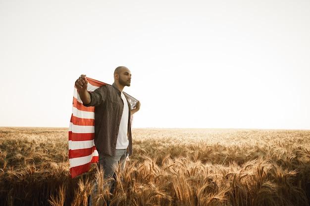 밀밭을 통해 미국 국기를 들고 아프리카계 미국인 젊은 남자