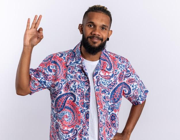 カラフルなシャツを着たアフリカ系アメリカ人の若い男が元気にokサインを示して笑顔のカメラを見て