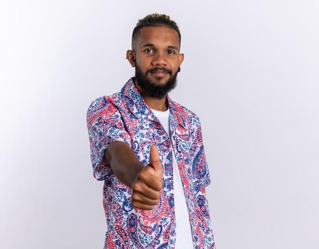 화려한 셔츠를 입은 아프리카계 미국인 청년은 흰색 배경 위에 엄지손가락을 들고 자신감 있게 웃고 있는 카메라를 바라보고 있다