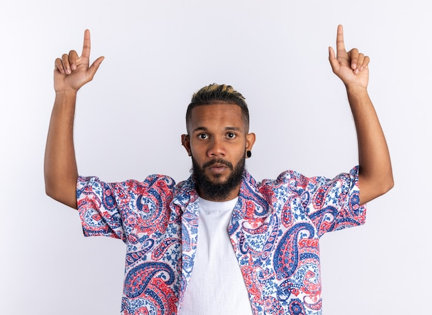 흰색 배경 위에 서 있는 검지 손가락으로 가리키는 카메라를 보고 있는 화려한 셔츠를 입은 아프리카계 미국인 청년