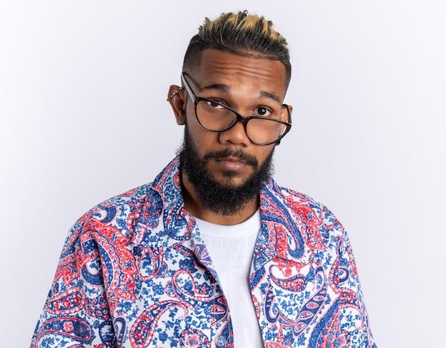 흰색 배경 위에 서 있는 혼란스러운 카메라를 바라보는 안경을 쓴 화려한 셔츠를 입은 아프리카계 미국인 청년