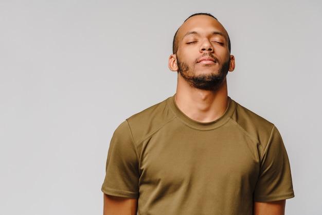 Афро-американский молодой человек в зеленой футболке над светло-серой стеной с закрытыми глазами с пустым пространством