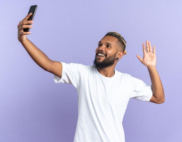 흰색 티셔츠에 아프리카 계 미국인 젊은 남자가 스마트 폰을 사용하여 셀카를하고 행복하고 밝은 손을 흔들며 웃고