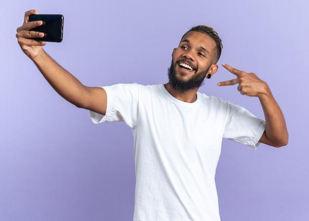 흰색 티셔츠를 입은 아프리카계 미국인 청년이 스마트폰으로 셀카를 찍고 파란색 배경 위에 v자 표시를 하며 즐겁게 웃고 있다