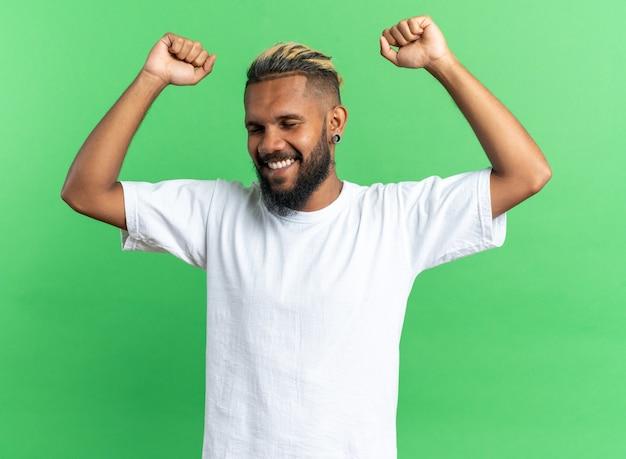 緑の背景の上に立って彼の成功を喜んで幸せで興奮した握りこぶしを握りしめる白いtシャツのアフリカ系アメリカ人の若い男