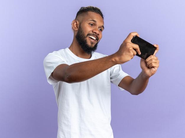 흰색 티셔츠를 입은 아프리카계 미국인 청년은 파란색 배경 위에 스마트폰을 사용하여 행복하고 즐거운 게임을 하고 있습니다.